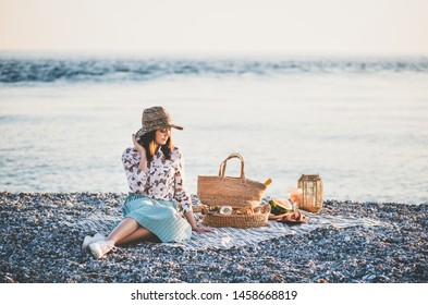 Summer beach picnic at sunset. Young woman in hat sitting on blanket and having weekend picnic outdoor at seaside with fresh seasonal fruit and tray of tasty appetizers