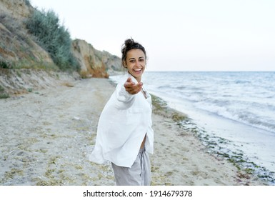 Summer beach portrait happy woman emotionally smile to camera, giving hand to camera like follow me