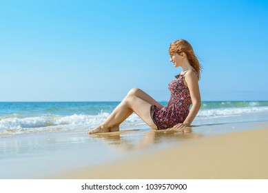 summer beach and pretty girl sitting on the sand and legs playing with waves and also running on the waves