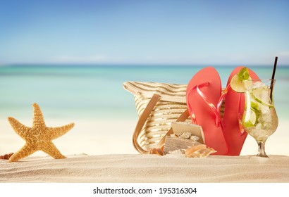 Summer beach with red sandals, drink and accessories