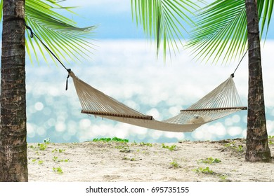 Summer beach relax with hammock on glowing bokeh from blue sea. Empty white hammock with sunhat and sunglasses in the shade between palm tree on tropical beach, vacation concept