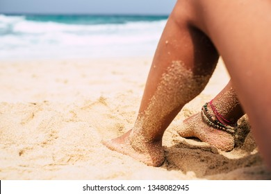 Summer and beach relax vacation concept with nude girl doing naturism nudism sit down on the sand enjoying the outdoor leisure activity - focus on bracelets at the feet - legs with sand