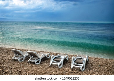 Summer beach scene with empty chairs at stormy weather