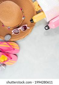 Plage d'été, accessoires de vacances en mer. Chapeau de paille, tongs colorés, aérosol jaune de protection du soleil et lunettes de soleil sur fond turquoise en pierre.