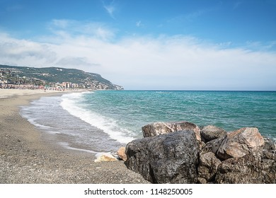Summer beach and soft wave background. Wonderful foamy waves on sea in Pietra Ligure, Liguria, Italy. Pebble beach.  Wave concept.