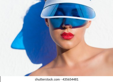 Summer beach style face lips close up portrait of a beautiful young woman wearing sun visor. Fashion beauty and make up cosmetics concept