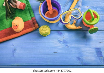 Summer beach toys on blue wooden background with copy space - top view