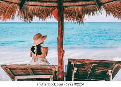 Summer beach travel vacation concept, Happy traveler asian woman with hat relax on chair beach at Koh Lipe, Satun, Thailand