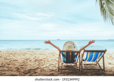 Summer beach travel vacation concept, Happy traveler asian woman with hat relax on chair beach at Pattaya, Chon Buri, Thailand