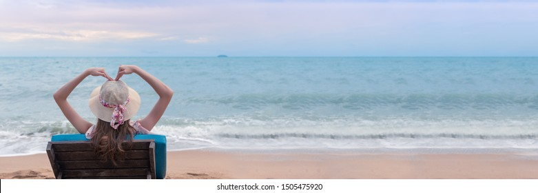 Summer beach travelling vacations, Happy traveller young woman sitting at beach chair and making hands heart shape with hands above head.