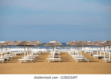 Summer beach with umbrellas and chaise lounges. Rimini resort. Italy.