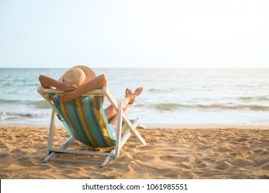 Summer beach vacation concept, Asia woman with hat relaxing and arm up on chair beach at Koh Mak, Trad, Thailand