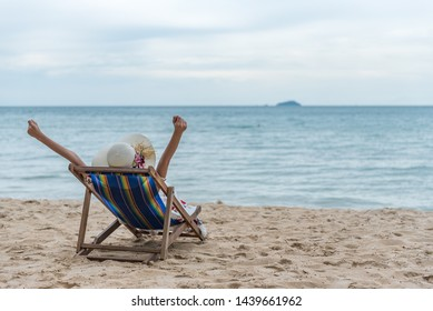 Summer beach vacation concept, Happy young Asian woman with hat relaxing on beach chair and raised hands up.