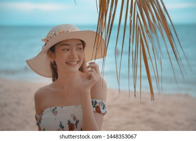 Summer beach vacation concept, Happy young Asian woman with hat relaxing on beach chai and raised hands up.