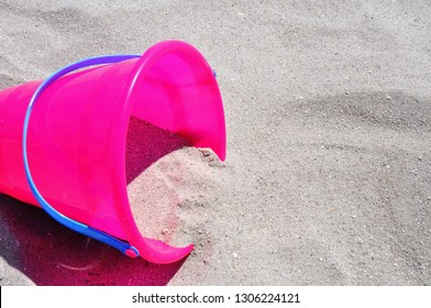 Summer beach vacation concept room for your text. Pink beach bucket with sand pouring out of it.
