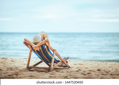 Summer beach vacation concept, Travel asian woman with hat and dress relax on chair beach at Pattaya, Chon Buri, Thailand