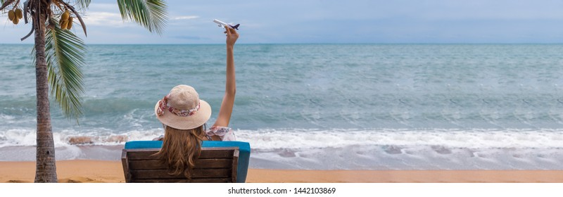 Summer beach vacation holidays trip concept, Happy young Asian woman with hat relaxing on beach chair and holding airplane model flying over blue sky.