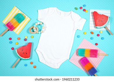 Summer beach vacation theme baby onesie romper bodysuit flatlay styled with watermelon and ice creams on a blue background. White product mock up with negative copy space for your text or design here.