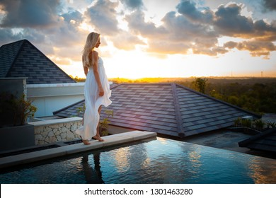summer beach vacation travel photo - young beautiful blonde bride girl in white dress standing on the top of the hotel resort near pool in tropical exotic bali on wedding on sunset or sunrise