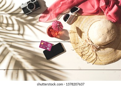 Summer beach vacations and tropical destinations: straw hat, sunglasses, credit card, smartphone and tropical foliage shadow