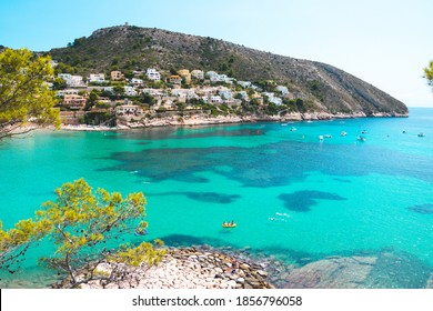 Summer at beautiful El Portet Beach with crystal clear turqouise waters in Moraira, Costa Blanca, Spain