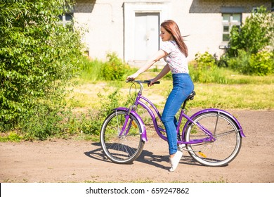 Summer. Beautiful woman with bicycle at the city park. Beautiful nature.
