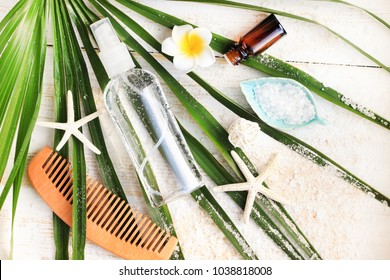 Summer beauty care kit. Bottle of mineral sea salt hair and body spray viewed from above on green palm leaf, comb, seastars and sandy wooden background.