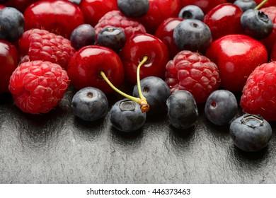Summer berries (blueberries, raspberries and cherries) on black background.