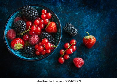 Summer berries in bowl on a table, fruits, raspberry, strawberry, red currant and mulberry