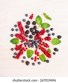 Summer berries and mint leaves composing  on white wooden background, top view