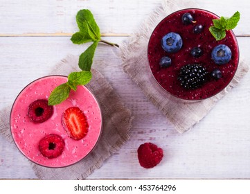 Summer berries smoothie  on white wooden background. View from above, top studio shot