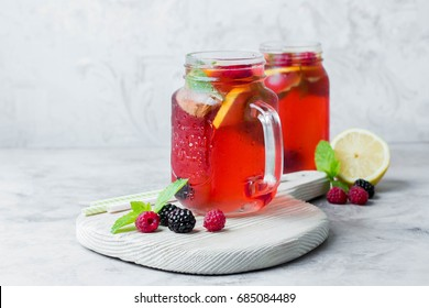 Summer Berry Drink. Lemonade with raspberry and blackberry with lemon, mint in mason jar on gray stone table background. Copy space, horizontal image