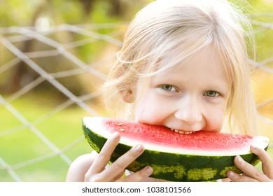 summer - blond little girl eating watermelon