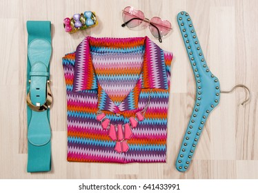 Summer blouse and accessories arranged on the floor. Woman colorful accessories, belt, sunglasses and bracelet with a chevron print top.