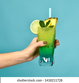 Summer blue and green tropical alcohol mojito cocktail drink with pineapple in woman hand on mint background