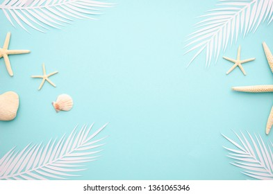 Summer blue and white topview flat lay background with tropical leaf, starfish and seashells