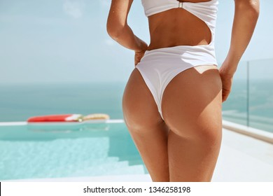 Summer body.  Woman's sexy ass in bikini swimsuit near infinity swimming pool at resort with sea on background. Female butt in panties outdoors