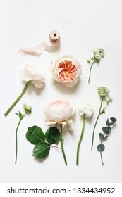 Summer botanical floral composition. Apricot English roses, ranunculus, astrantia  flowers, eucalyptus branch and pink ribbon on white table background. Styled stock photo. Vertical flat lay, top view