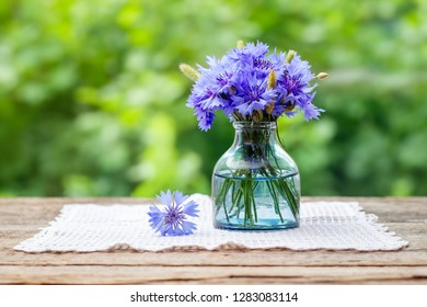 Summer bouquet of blue cornflower on wooden board outdoors with copy space.