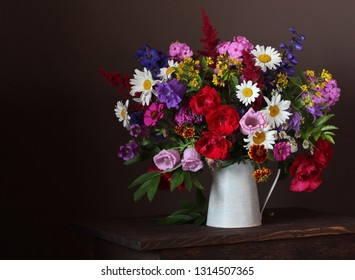 summer bouquet in a jar: roses, daisies, Phlox, bells and other garden flowers on a dark background.