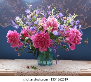 summer bouquet of pink peonies and irises in a glass vase on a blue background. country still life.