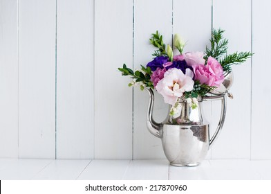 Summer bouquet of purple and pink eustomas in an antique coffee pot on a white wooden board, vintage style, holiday and wedding floral background