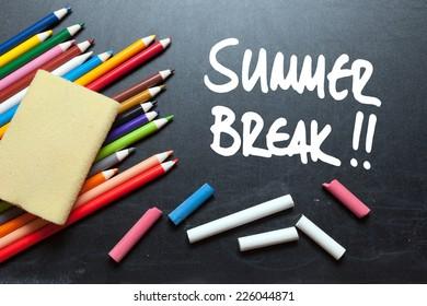 Summer break written on a blackboard with school tools around