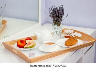 Summer breakfast. A cup of tea, fruits and pastries on a wooden tray.