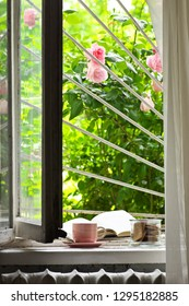 Summer breakfast in farmhouse: cup of coffee, cookies and open book on old wooden windowsill against garden with blooming roses.