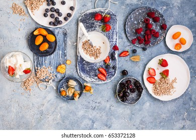 Summer breakfast food concept with dairy product, oatmeal cereal, berry and fruits. Overhead of breakfast blue table with yogurt, kefir oatmeals, mix berry and fruits.