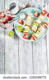 Summer breakfast snack. Fruit vegan dessert kebabs on skewers with toast French fried bread, fruits and berries. With powdered sugar and chocolate sauce.