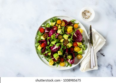 summer bright fresh salad of cherry tomatoes, avocado and radicchio leaves on a white marble table. concept of healthy eating. copy space