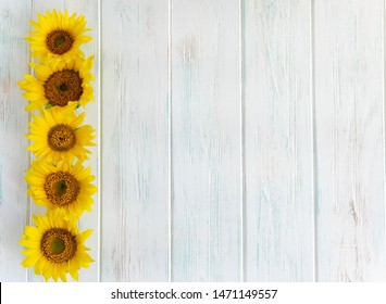 Summer bright light wooden background with flowers of sunflowers on the sides. Frame for text with sunflowers. Greeting card with flowers view from the top.