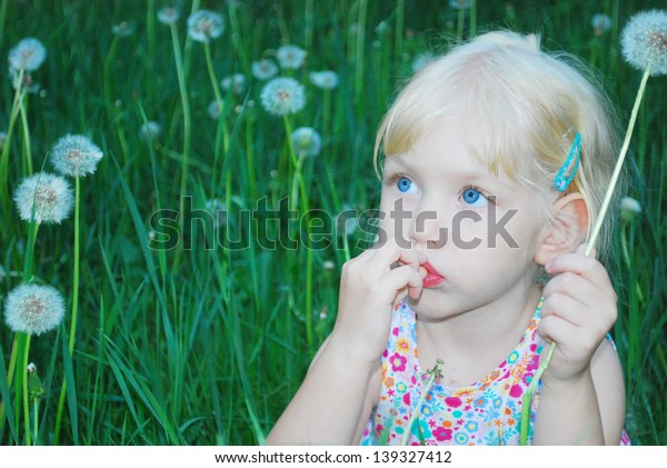 In the summer, bright sunny day, in  forest in the meadow;, a little  girl is sitting in the tall grass and flowers dandelion